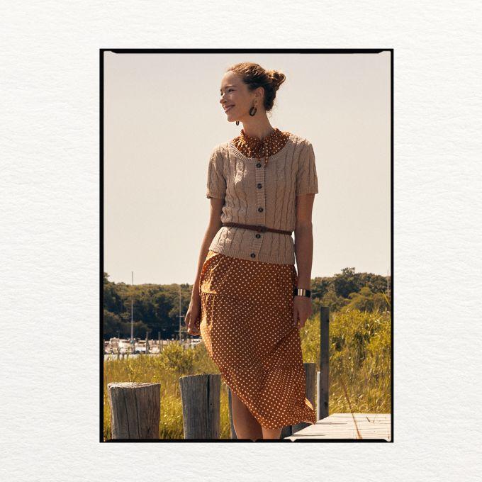 Woman in orange polk-a-dot dress, ribbed cream knit wear sweater and belt.