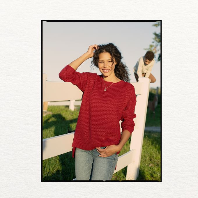 Woman in red ripped knit wear sweater and jeans.