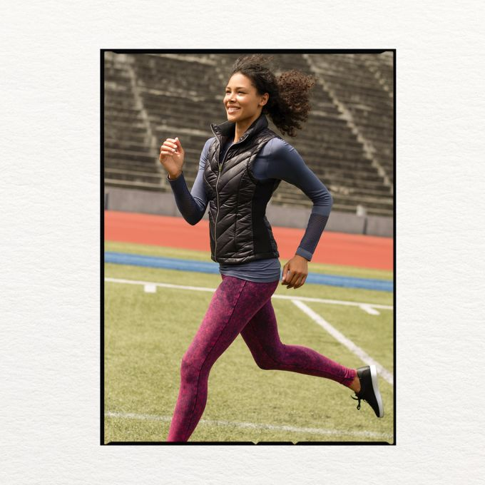 Woman running outside in activewear.