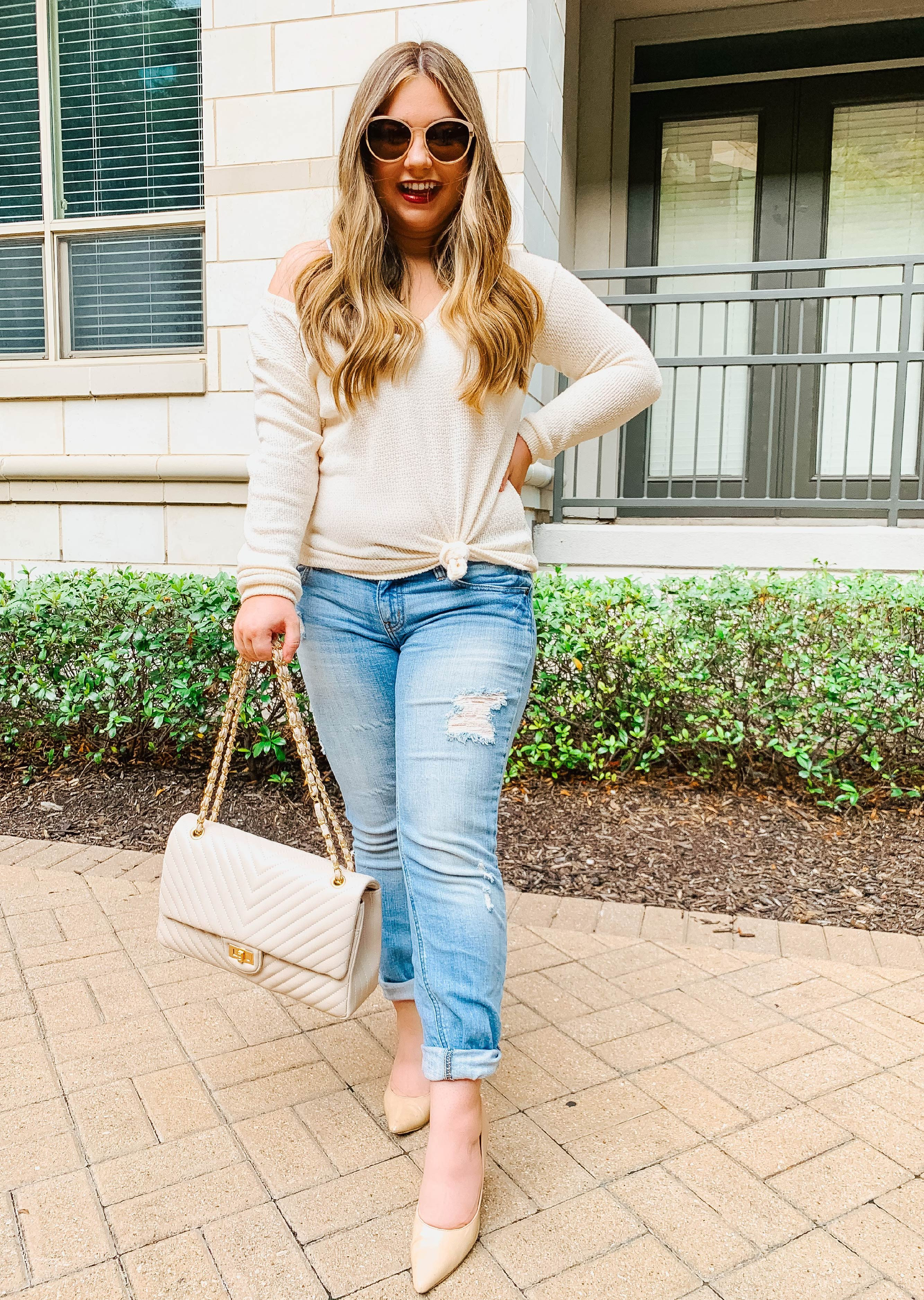 Look 2 - Cream sweater tied in a side front knot, a little off the shoulder. Paired with light wash denim, and cream purse with gold accents.