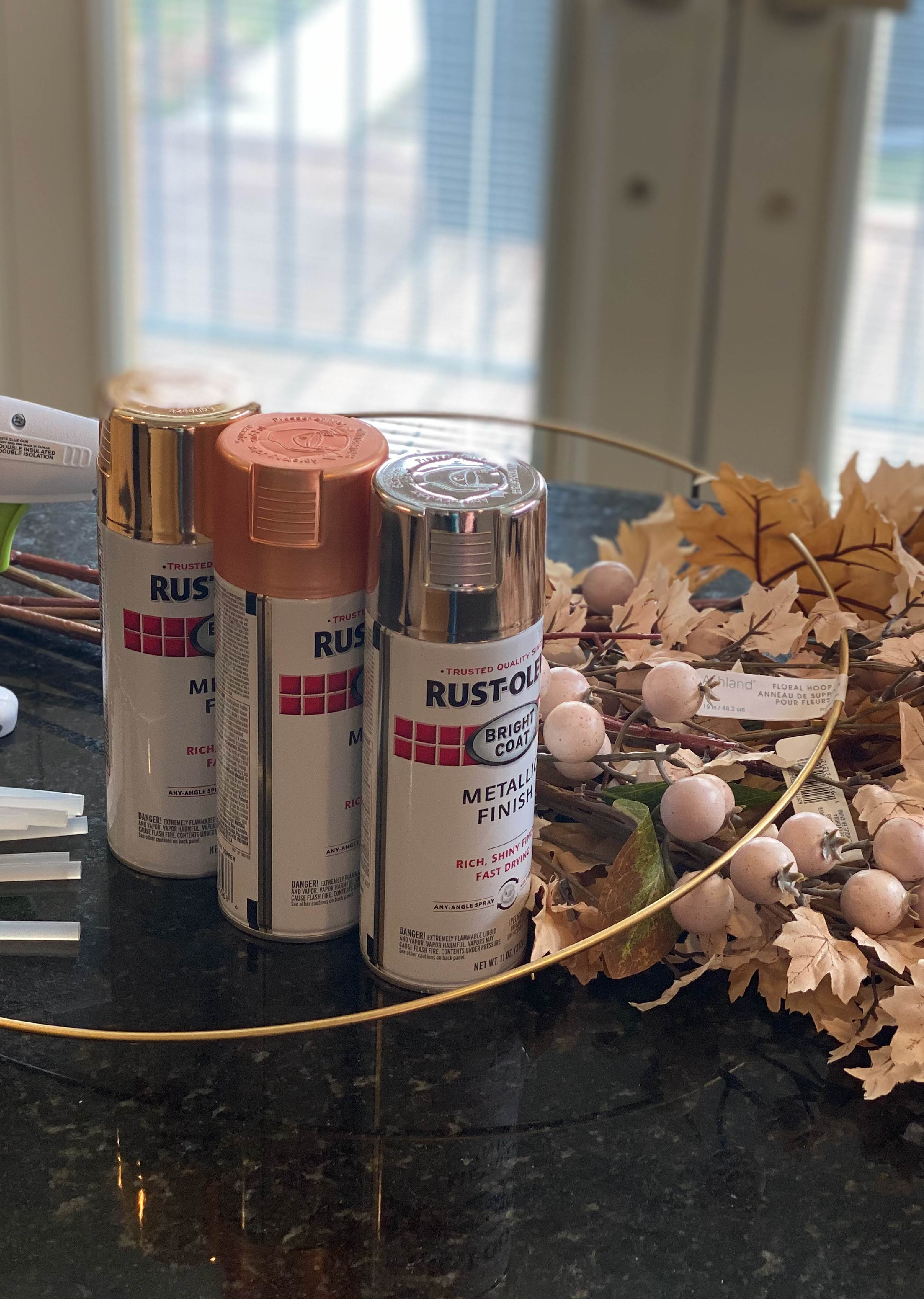 Picture of spray paint cans, glue gun, gold wire for wreath, and fake leaves.