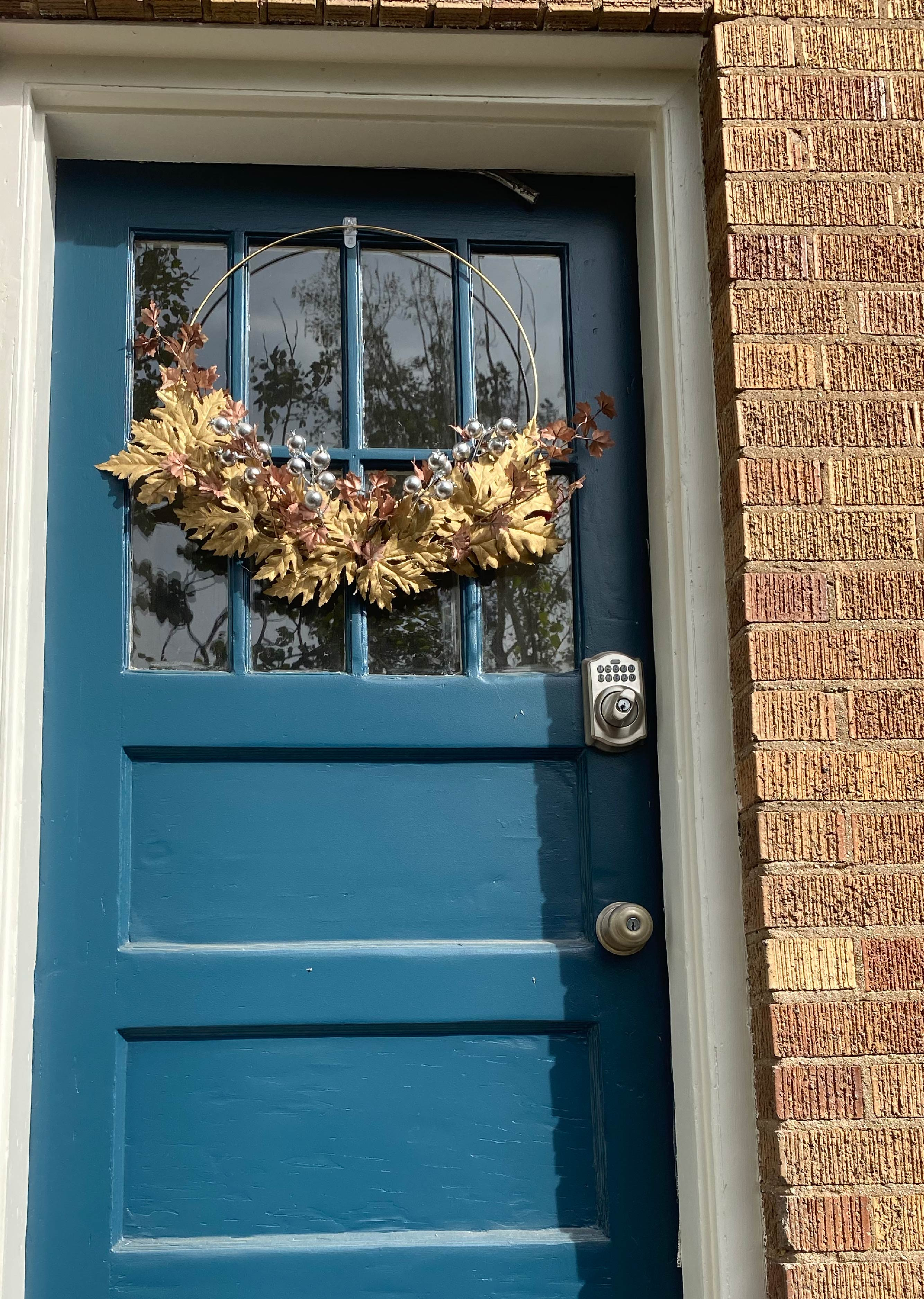 Picture of finished wreath on blue door.