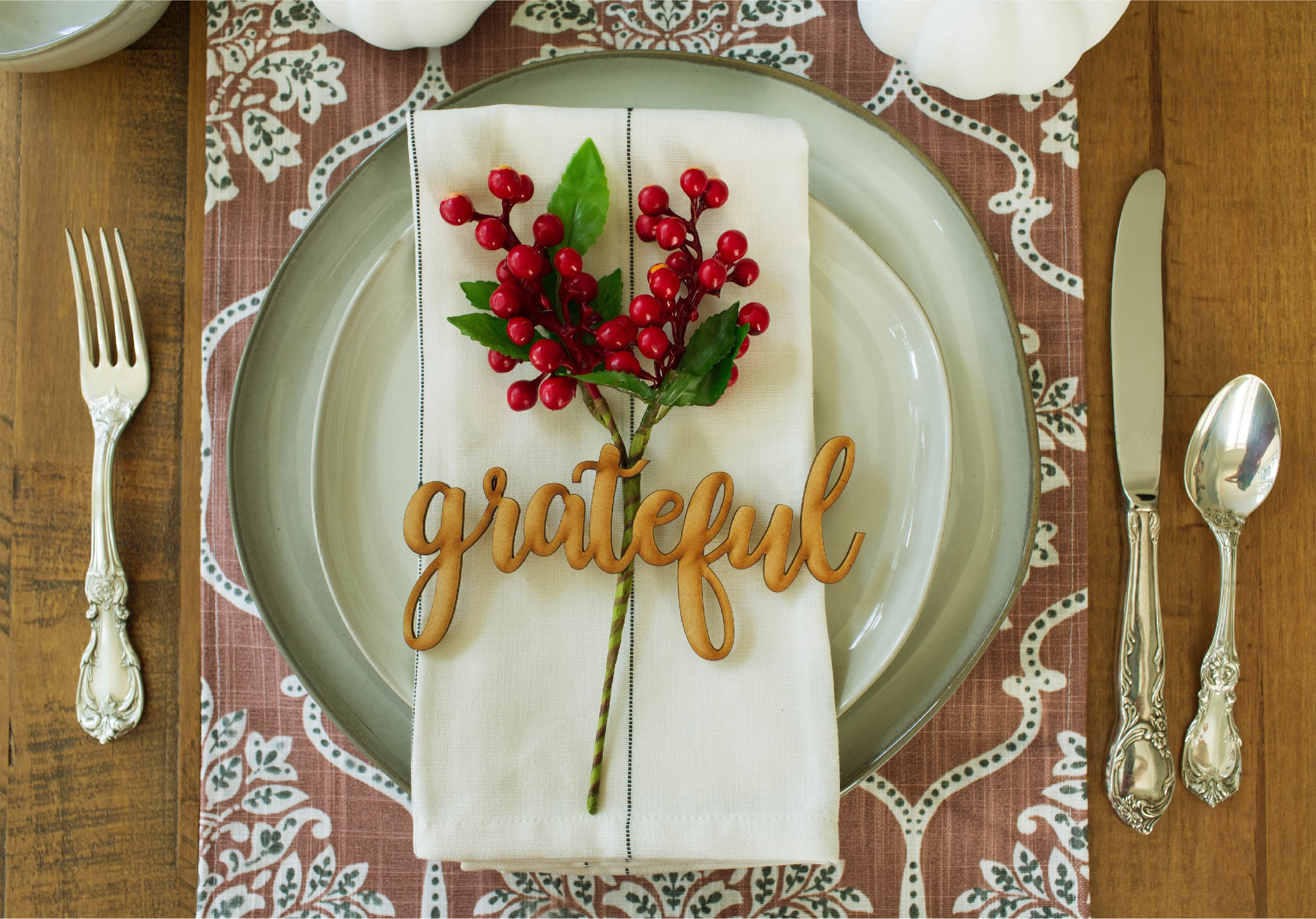 Close up of place setting highlighting the napkin placing with the wood words grateful styled with holly berries.