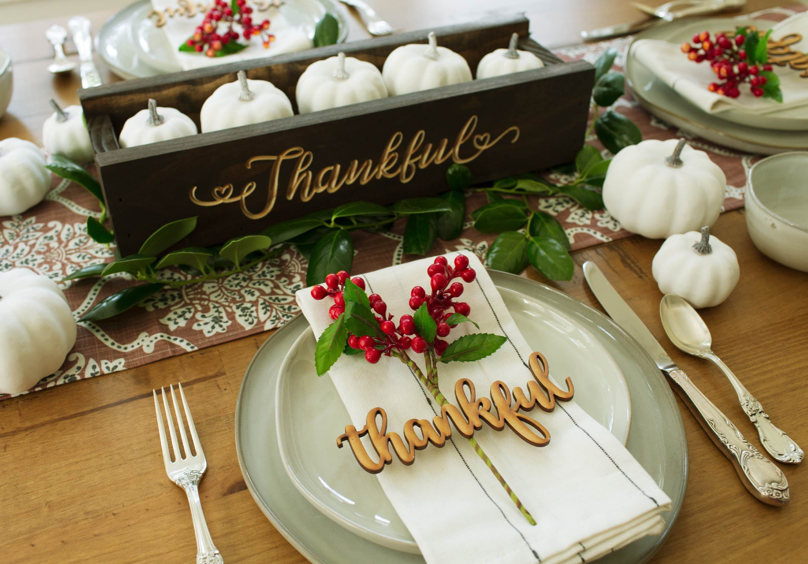 Thanksgiving Tablescape with place setting, table runner, center piece, and white gourds laid around.