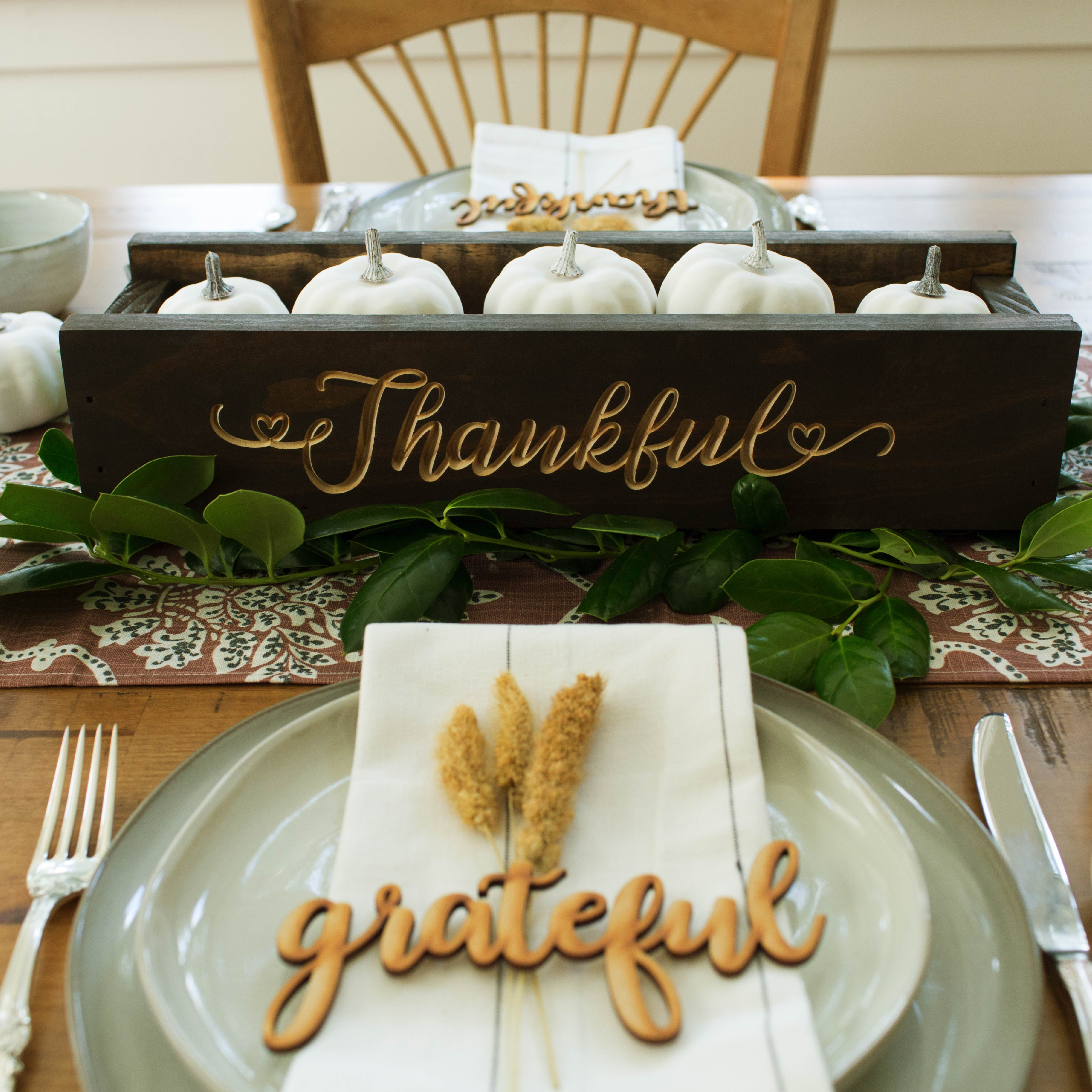 Close up of centerpiece. A wood box with white gourds inside and the word Thankful carved on the side.
