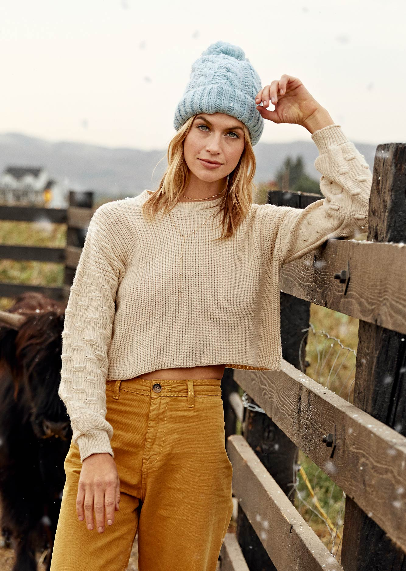 Picture of a women wearing a blue beanie, cream sweater and yellow jeans.