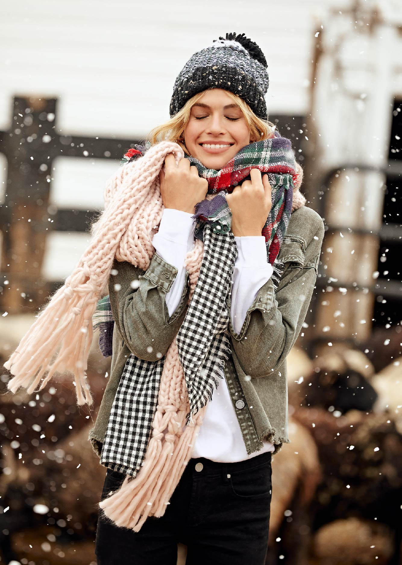 Women holding scarves with a beanie. Scarves are plaid, pink, and buffalo check.