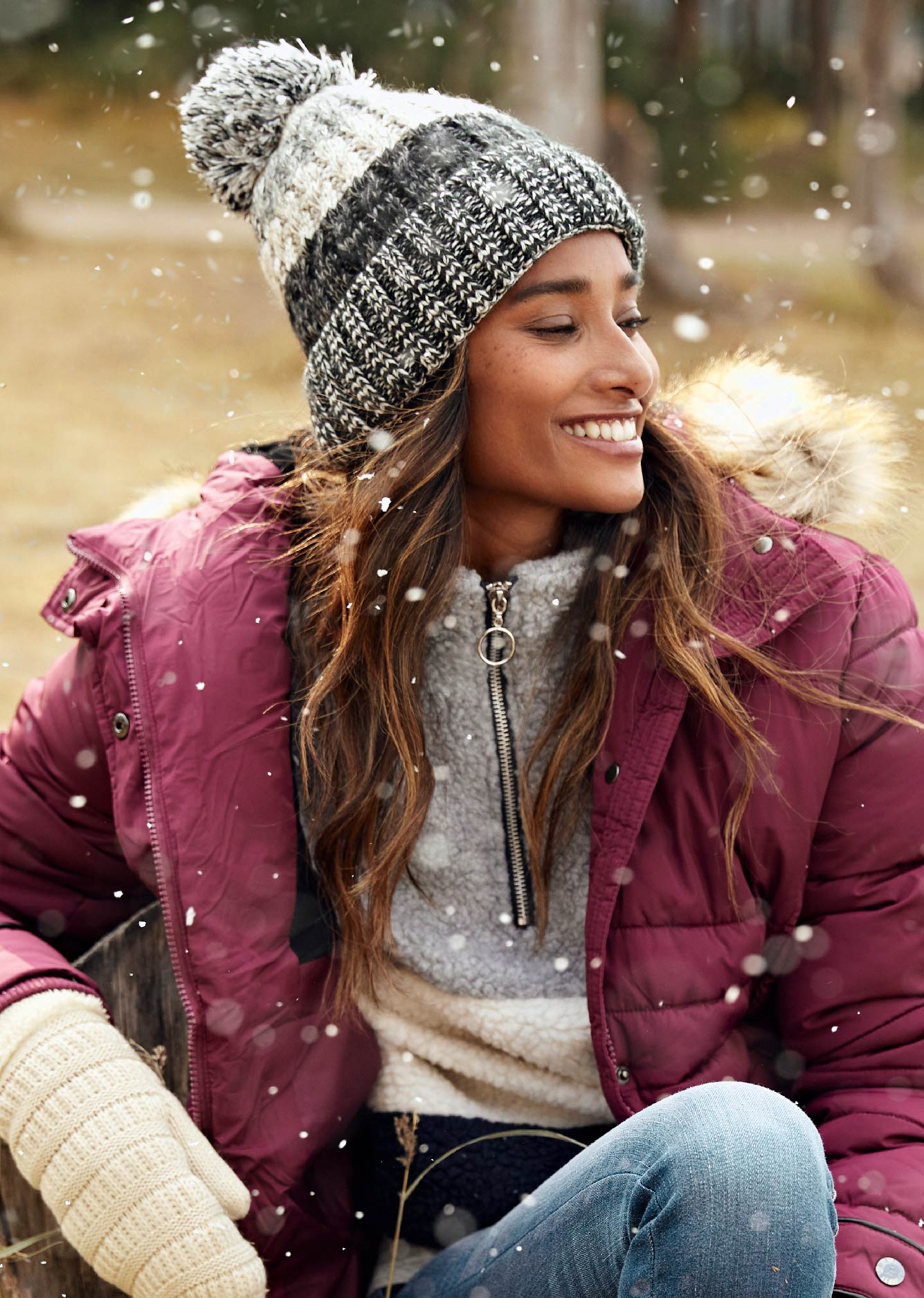 Women wearing a grey, charcoal, and cream striped beanie. Purple jacket with shearling 3/4 zip pullover.